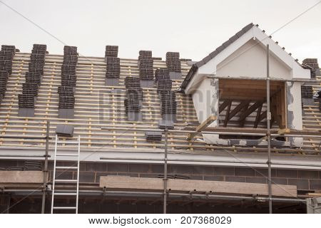 working on the roof sheeting and outriggers or ladder of a new, two story, commercial apartment building in the UK