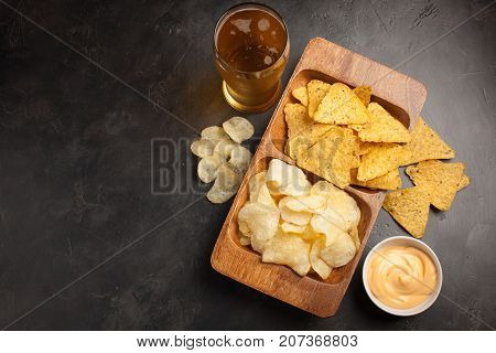 Beer In Glasses Closeup On The Concrete Table. Beer And Snacks Are Chips And Nachos In Wooden Bowl W