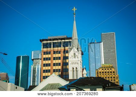 religious steeple cross on top of buildings in Houston Texas Downtown Skyline on a nice blue sky day