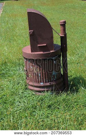 Brown metal trash can altered to be bear-proof, vertical aspect