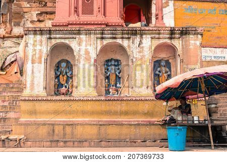 VARANASI INDIA - MARCH 14 2016: Front picture of colorful temple with God Images at Dashashwamedh Ghat in front of Ganges River in the city of Varanasi in India