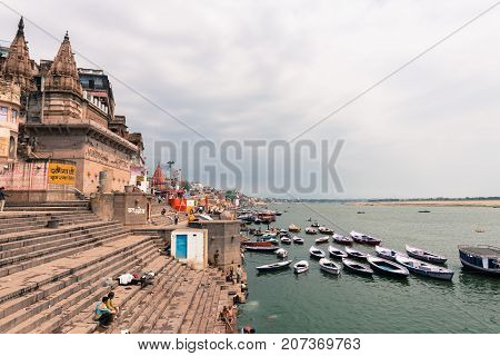VARANASI INDIA - MARCH 14 2016: Horizontal picture of the stairs of Munshi Ghat and the holy Ganges River with many boats in the city of Varanasi in India