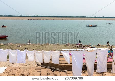 VARANASI INDIA - MARCH 14 2016: Horizontal picture of white cloths on the clothesline in front of Ganges River in the city of Varanasi in India