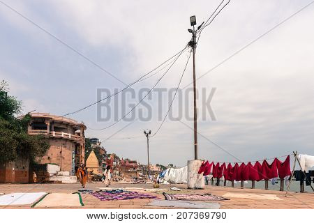 VARANASI INDIA - MARCH 14 2016: Wide angle picture clothes getting dry at Narad Ghat in front of Ganges River in the city of Varanasi in India
