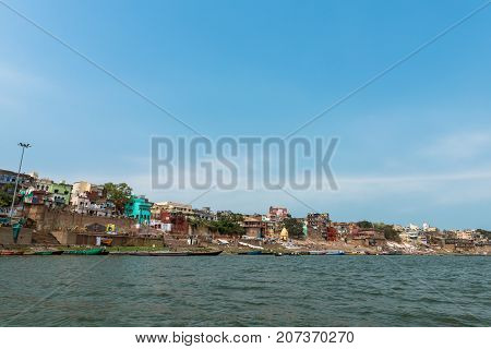 VARANASI INDIA - MARCH 14 2016: From the boat wide angle picture of Ganges River during sunny day in the city of Varanasi in India