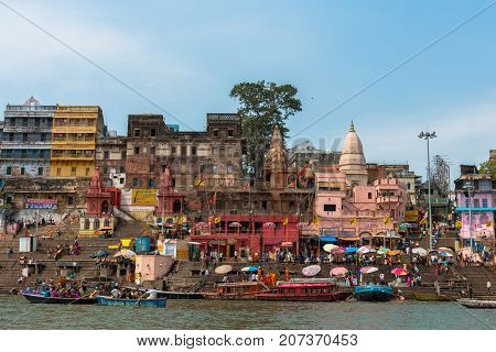 VARANASI INDIA - MARCH 14 2016: Wide angle picture of boats in front of Dashashwamedh Ghat in Ganges River during day time in Varanasi India.