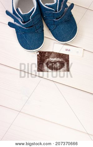 Pregnancy Test, Ultrasound Scan Of Baby And Baby Shoes Lying On Boards, Expecting For Baby