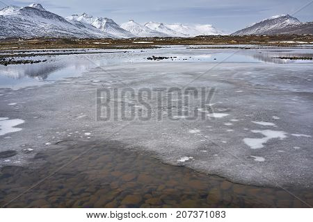 Tranquil shallow river with ice islets and rocky bottom on the background of the snowy mountains and cloudy sky in Iceland. Panoramic horizontal photo.