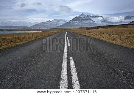 County roadway between the brown fields with rocks and sea shore on the background of the snow mountains and cloudy sky in Iceland. Horizontal.