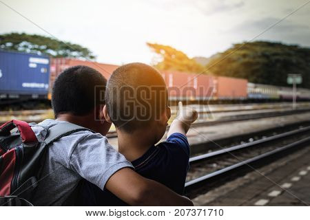 Brother and brother are looking train at train station in Thailand.