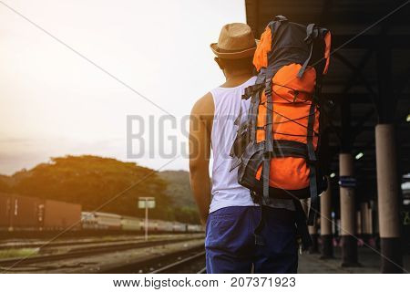 Back of man backpack walking at train station in Thailand.