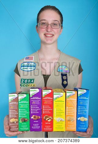 Alameda CA - October 04 2017: Cadette Girl Scout holding boxes of Girl Scout cookies. Girl Scout cookie sales help girls learn marketing and money management skills.