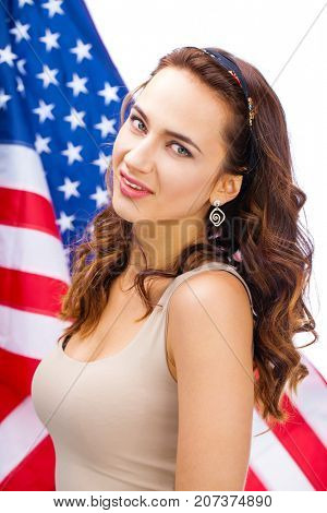 Portrait of a young beautiful woman against the background of the American flag