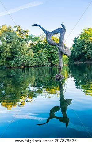 LONDON, ENGLAND - AUGUST 6, 2017; Cormorant sits alone atop bird sculpture reflected in Victoria Lake London UK