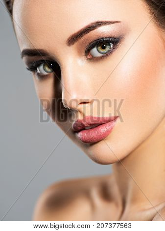 Beauty face of the young beautiful woman. Gorgeous female portrait. Young adult girl with healthy skin. Pretty lady with fashion eye makeup.