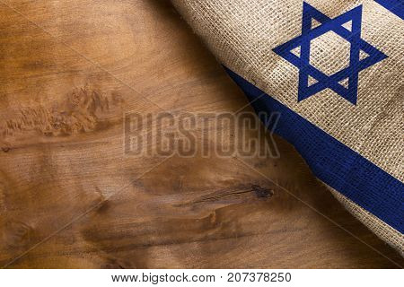 Flag of the State of Israel from rough fabric on a wooden surface