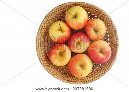 Top view of small gala apple in basket over white background.