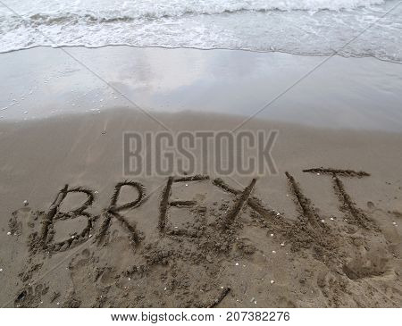 Text Brexit On The Sand Of The Sea Waiting To Be Erased By The W