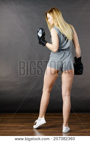 Sportsmanship fairplay and strong body. Young slim woman fighting boxing. Blonde girl wearing black punch gloves posing in full length. Sport and fitness power exercising. Back view