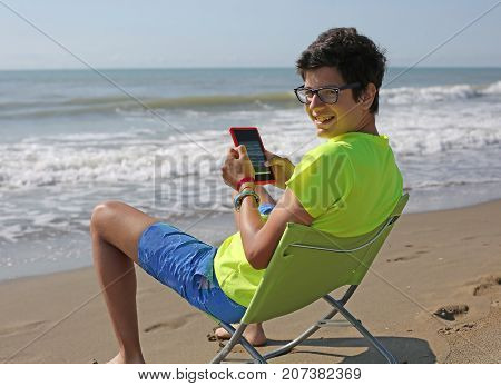 Young Smiling Caucasian Boy Reads An Ebook Sitting On The Beach