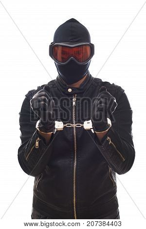 Dangerous criminal wearing black clothes and mask with handcuffs on isolated background