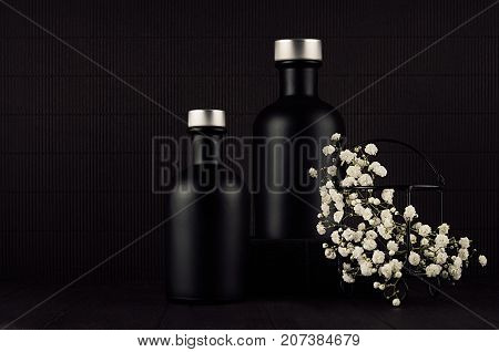 Noir exquisite home decor with blank black cosmetics bottles white small flowers on dark wood board mock up. Dark black minimalist interior for advertising designers branding identity cover.