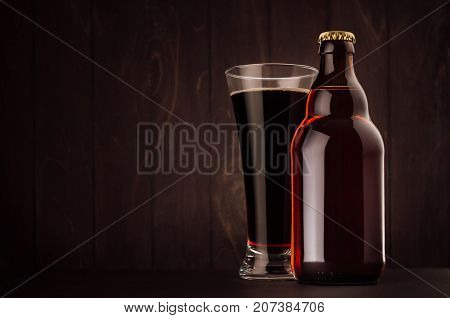 Brown beer bottle belgian steinie and glass pilsner with porter on dark wood board copy space mock up. Template for advertising design branding identity.