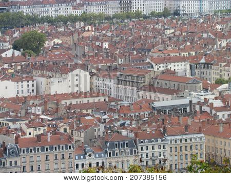 Aerial view of a cityscpae of downtown Lyon in France with plenty of red roofs and white old buildings