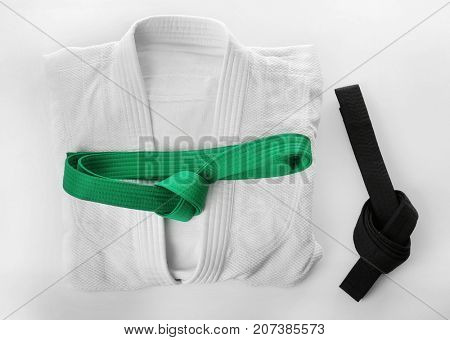 Karate uniform with black and green belts on white background