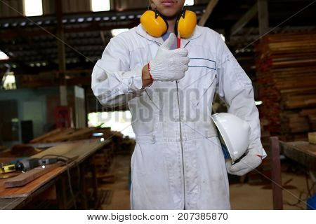 Portrait of confident young carpenter in white uniform showing thump up with pencil tools in carpentry workshop.