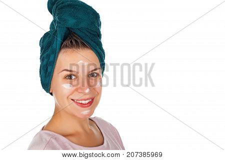 Happy female with facial moisturizer and bathtowel smiling at the camera on isolated background