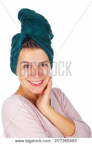 Beautiful young female with bath towel on head smiling at the camera on isolated background