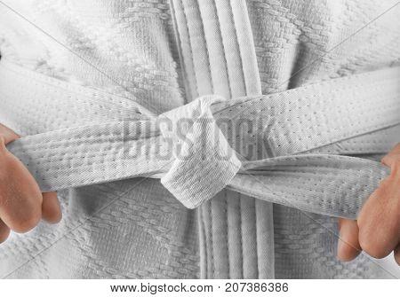 Man in karategi tying white belt, closeup