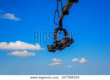 Professional camcorder on a crane against a blue sky. technology. space for text