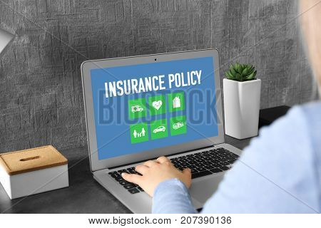 Woman using laptop at table. Concept of insurance policy