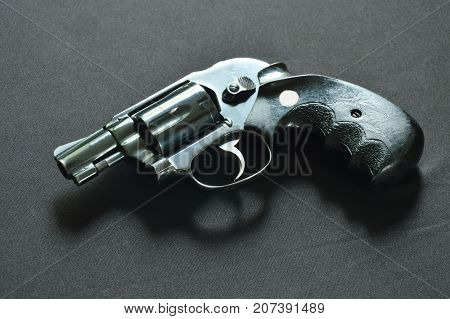 revolver gun on the black fabric background