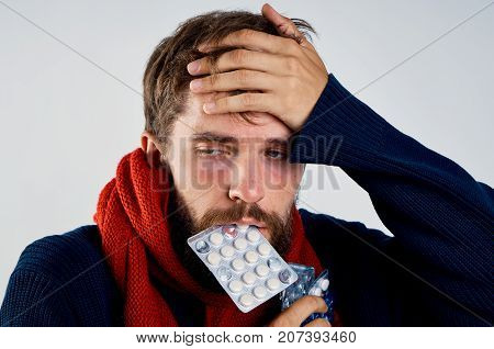 man holds in his mouth a pack of pills, fatigue, sickness, sick.
