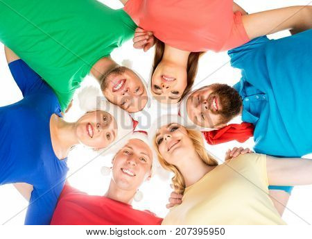 Team of happy young people in Christmas hats celebrating Christmas or New Year. Friends embracing together isolated on white. X-mas, Xmas concept.