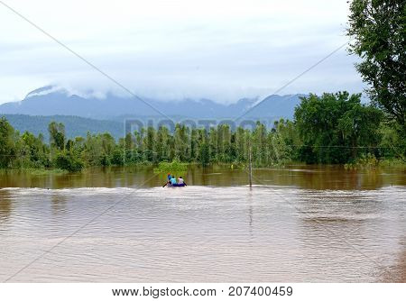 Phitsanulok Thailand- September 162017: Flash flood by red turbid water flows down from the mountain due to torrential rain with people paddling boats.