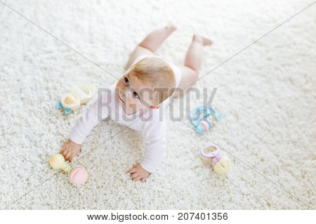 Cute baby playing with colorful pastel vintage rattle toy. New born child, little girl looking at the camera and crawling. Family, new life, childhood, beginning concept. Baby learning grab