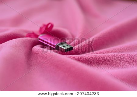 Brilliant Pink Usb Flash Memory Card With A Pink Bow Lies On A Blanket Of Soft And Furry Light Pink