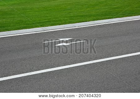 Markings road with arrows and green grass. Road surface, white lines on asphalt, green grass - all this creates the background.