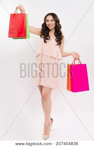 Beautiful woman carrying colorful shopping bags and looking up