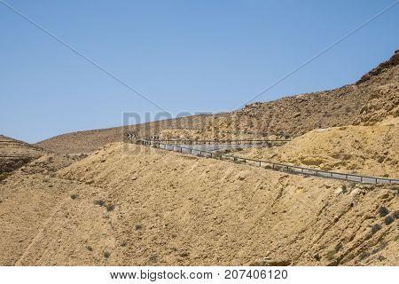 Serpentine road in the desert Negev descending into a large crater Ha-Gadol (Israel)