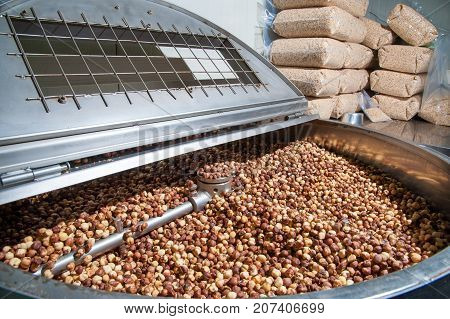 Shelled hazelnuts inside the machine for the peeling and blanching precess poster