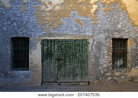 Old wooden gates and two grating windows. Weathered wall of derelict house