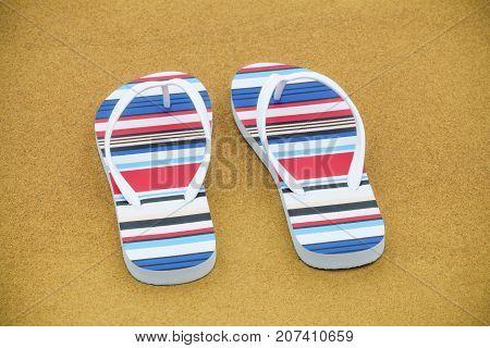 Flip flops on the sandy beach in summer day
