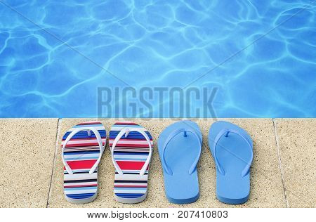 Flip flops near swimming pool in summer day