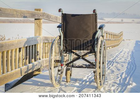 Wheelchair on bridge near lake in winter .