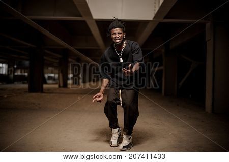 Emotional and gesticulating young afro american guy dressed in black clothes and white sport shoes. Full length